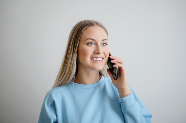 Woman in blue top on the phone.