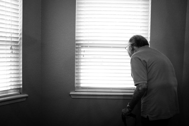 A black and white photograph of an old man looking out the window.